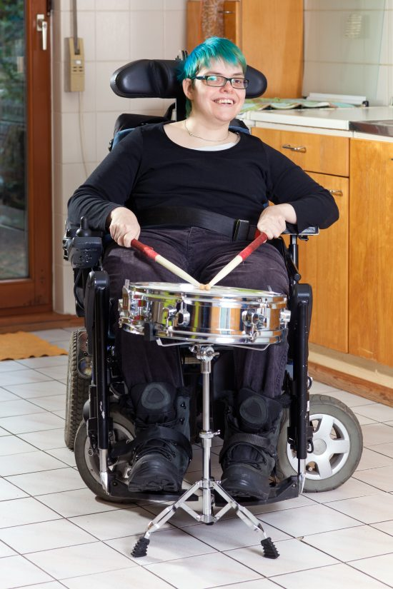 Happy spastic young woman with infantile cerebral palsy due to birth complications confined to a multifunctional wheelchair, beating on a drum as part of her therapy smiling at the camera.