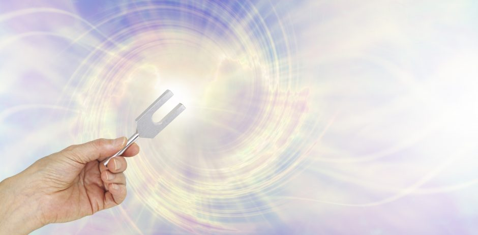 Female hand holding a short aluminum tuning fork on a graphic depiction of angelic sound waves background